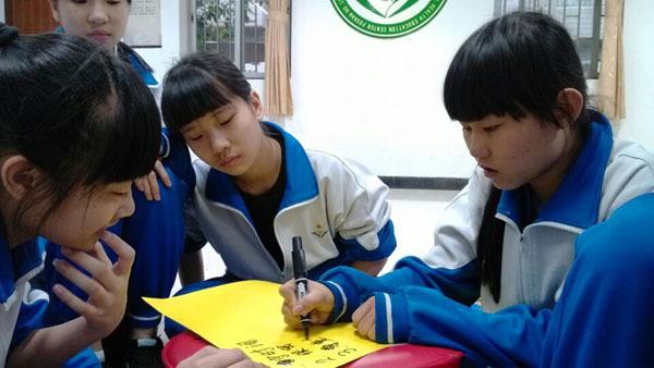 图片二:小组成员在认真撰写我们的约定