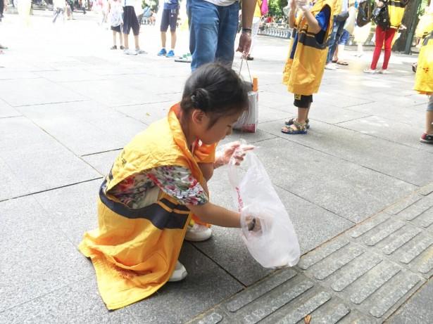 小小志愿者捡起污染公园的垃圾。