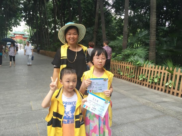 小小志愿者手持环保宣传单张。