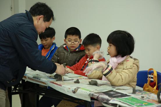 图一:黄老师指导成员进行陶艺创作