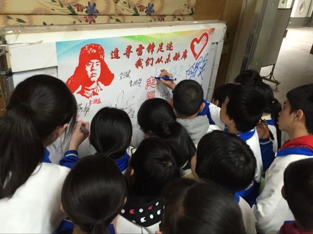 """志愿者们在""""粤志愿,越幸福""""签名墙上写下自己的名字"""